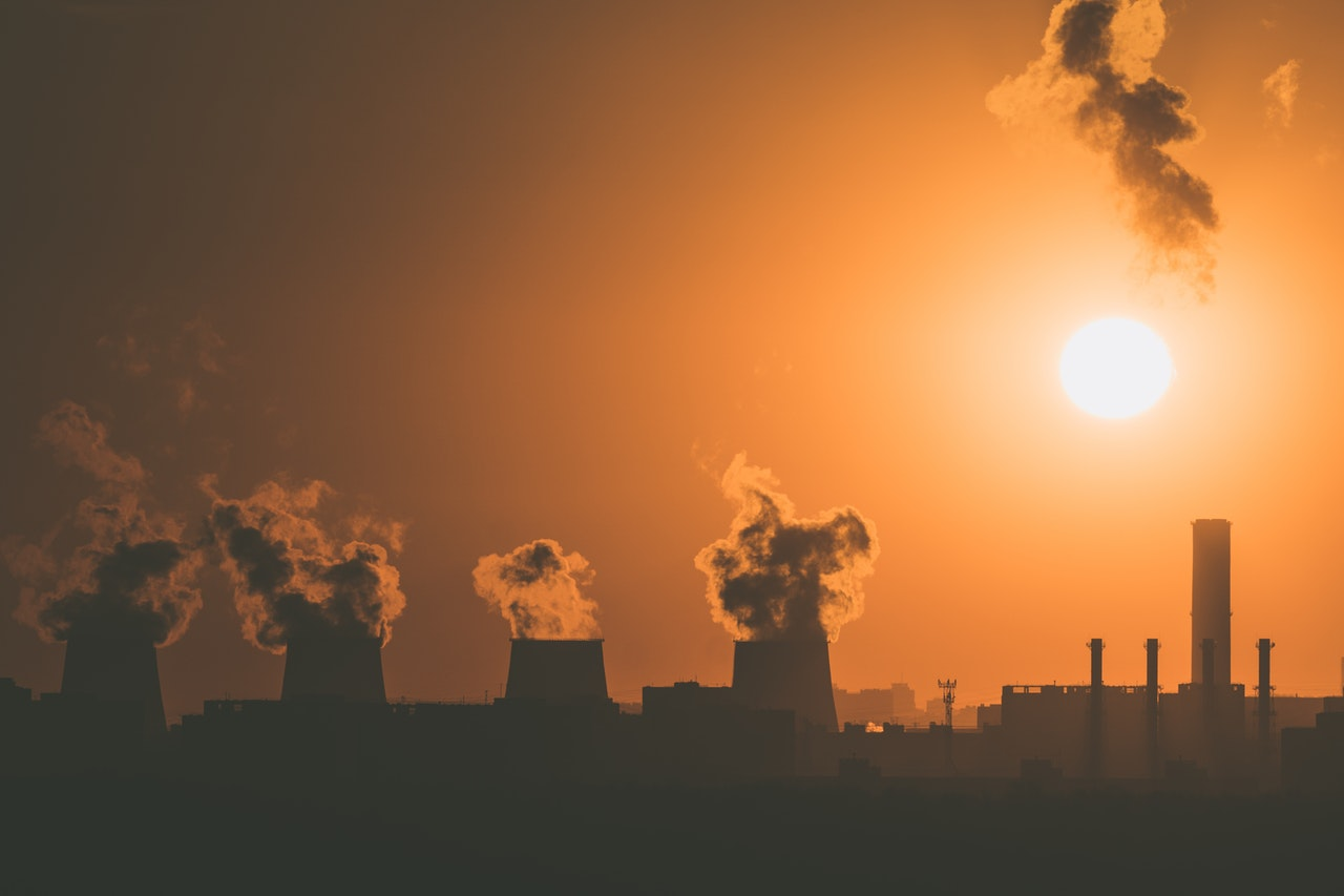 A fossil fuel burning industrial plant silhouetted against the setting sun